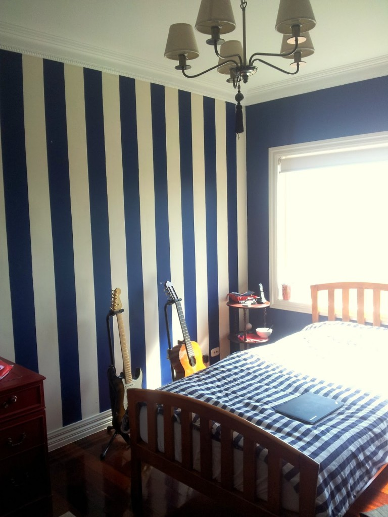 other-design-classy-brushed-bronze-ceiling-lighting-over-blue-quilt-rail-headboard-bed-and-blu-striped-wall-decals-as-decorate-in-guys-navy-blue-bedroom-ideas-soothing-navy-blue-bedroom-with-wall-deco